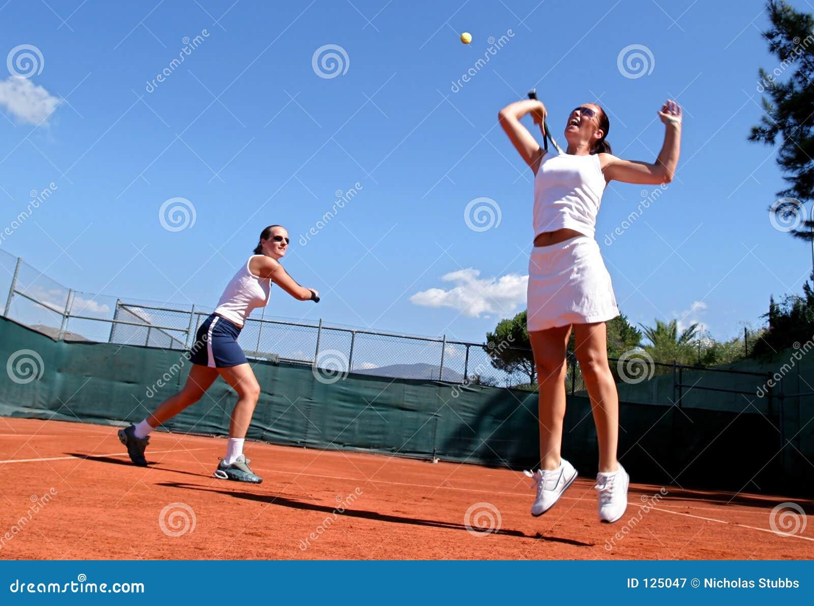 Twee vrouwelijke tennisspelers die dubbelen in de zon spelen. Men springt en rekt zich voor de bal uit.