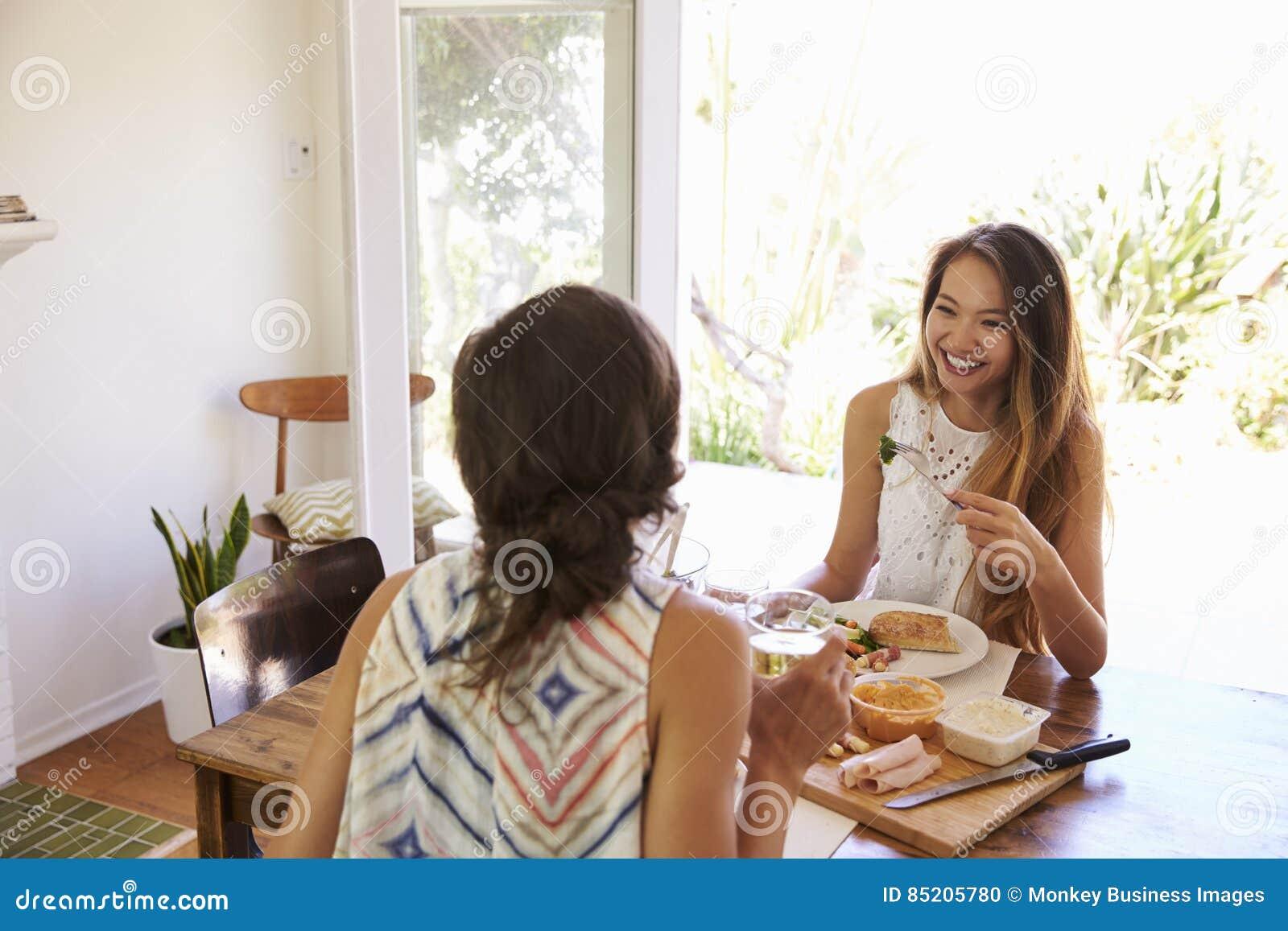 Twee Vrouwelijke Vrienden die van Maaltijd thuis samen genieten