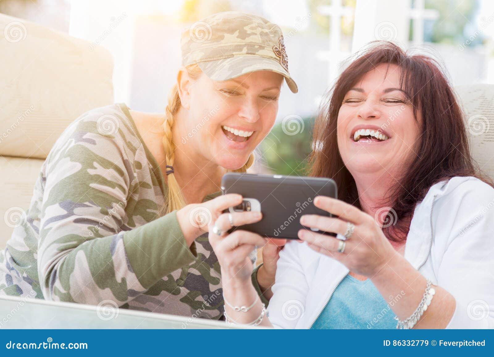 Twee Vrouwelijke Vrienden lachen terwijl het Gebruiken van een Slimme Telefoon