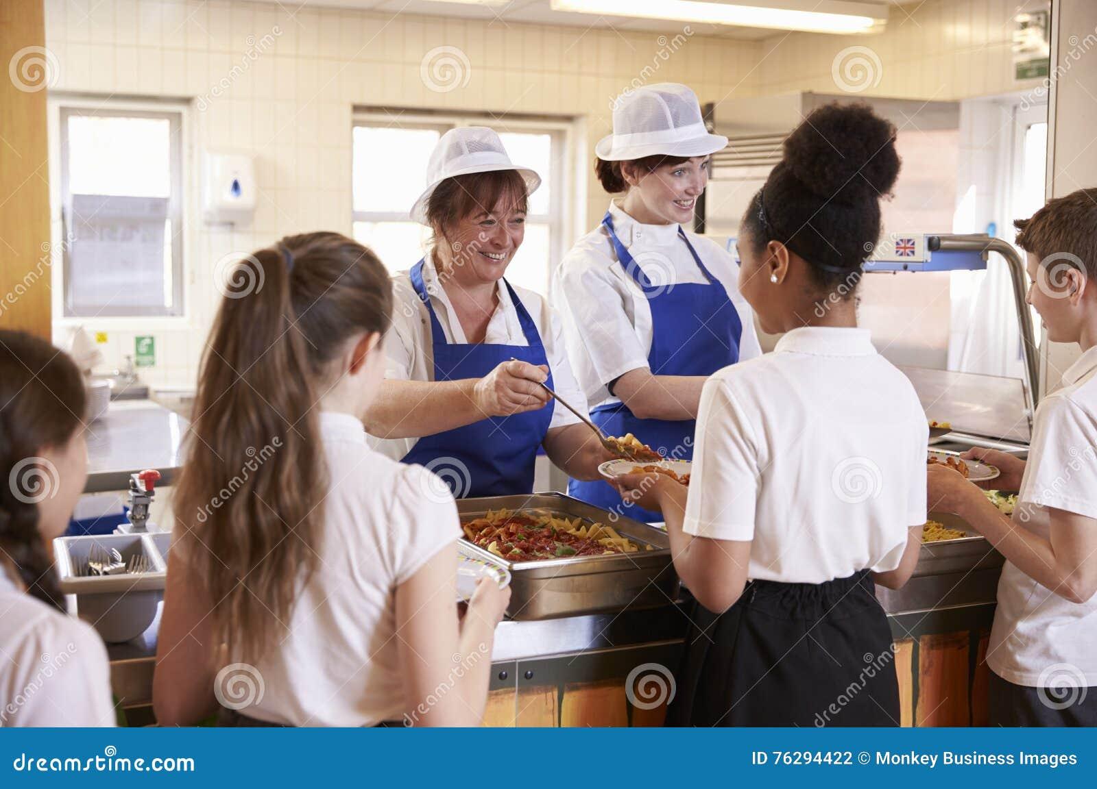 Twee vrouwen die jonge geitjesvoedsel in een schoolcafetaria dienen, achtermening
