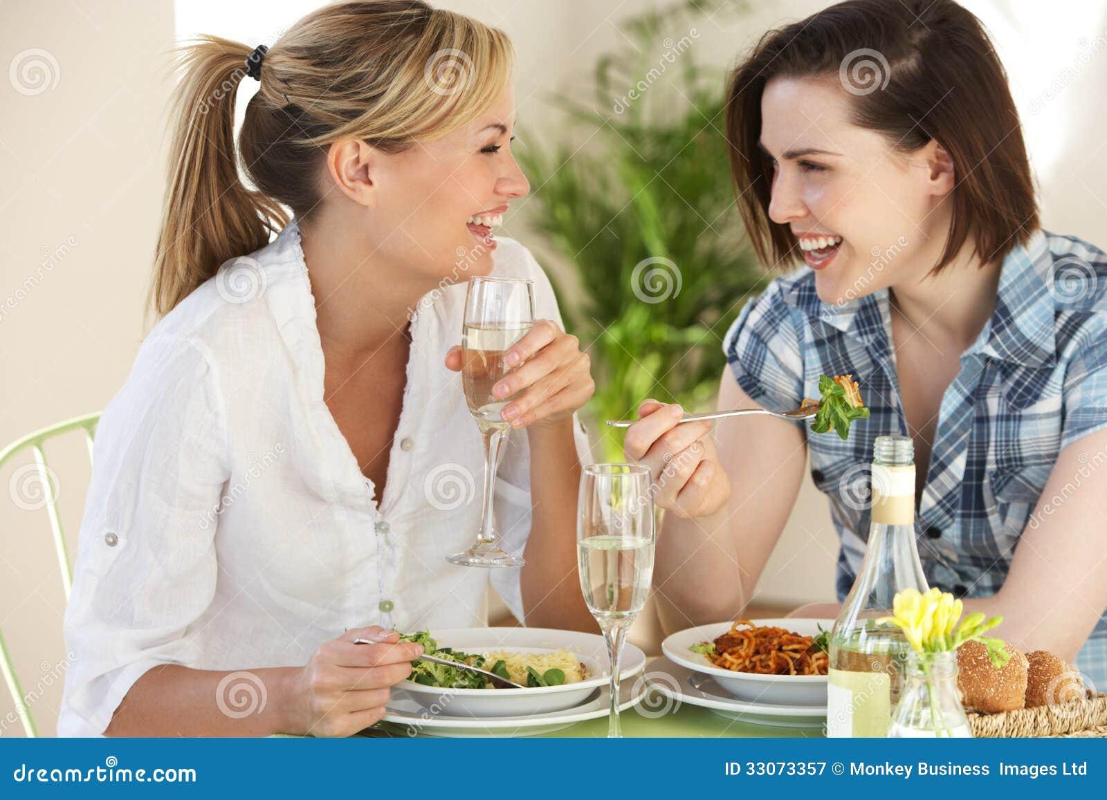 Twee Vrouwen die Maaltijd in Koffie hebben