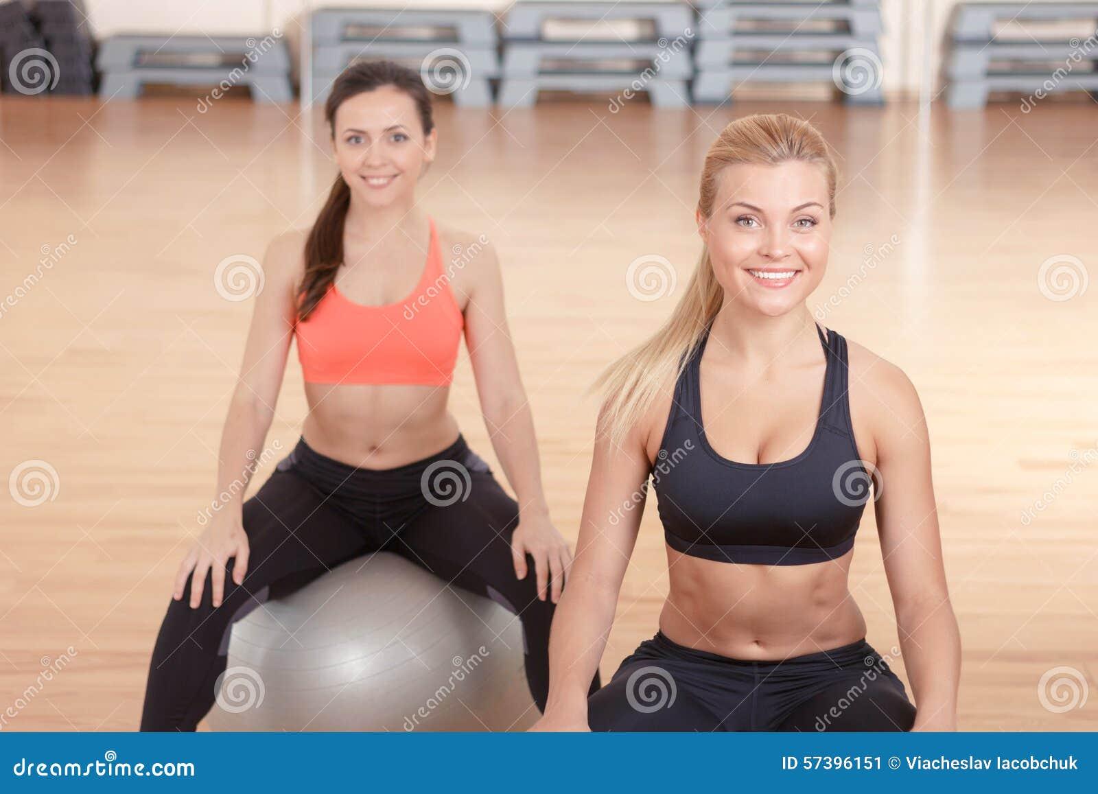 Twee vrouwen die op bal voor geschiktheid zitten
