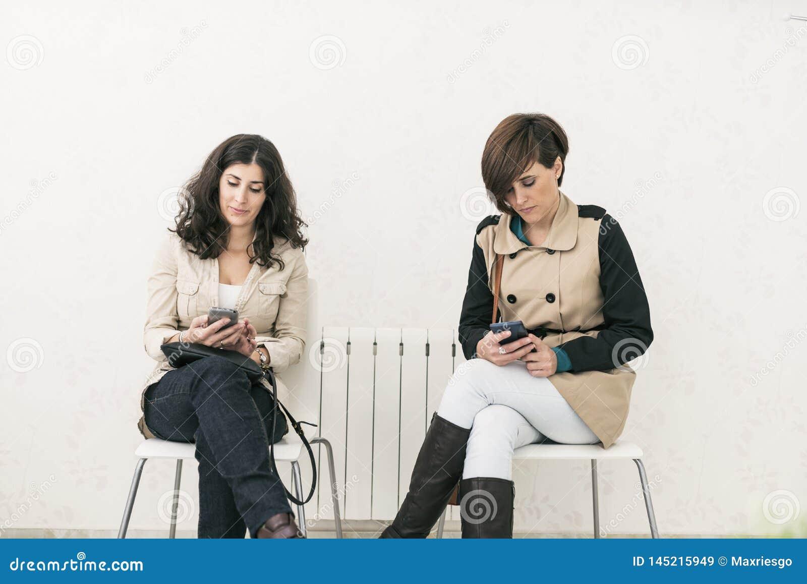 Twee vrouwen die in wachtkamer ernstige smartphone kijken
