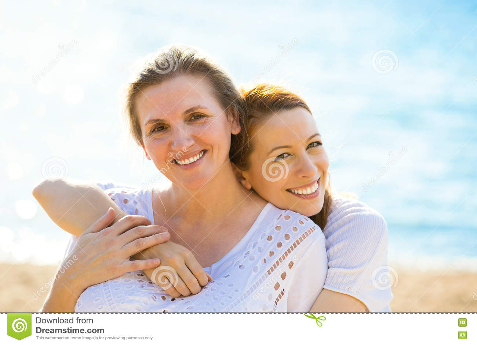 Twee vrouwenmoeder en volwassen dochter die van vakantie op het strand genieten