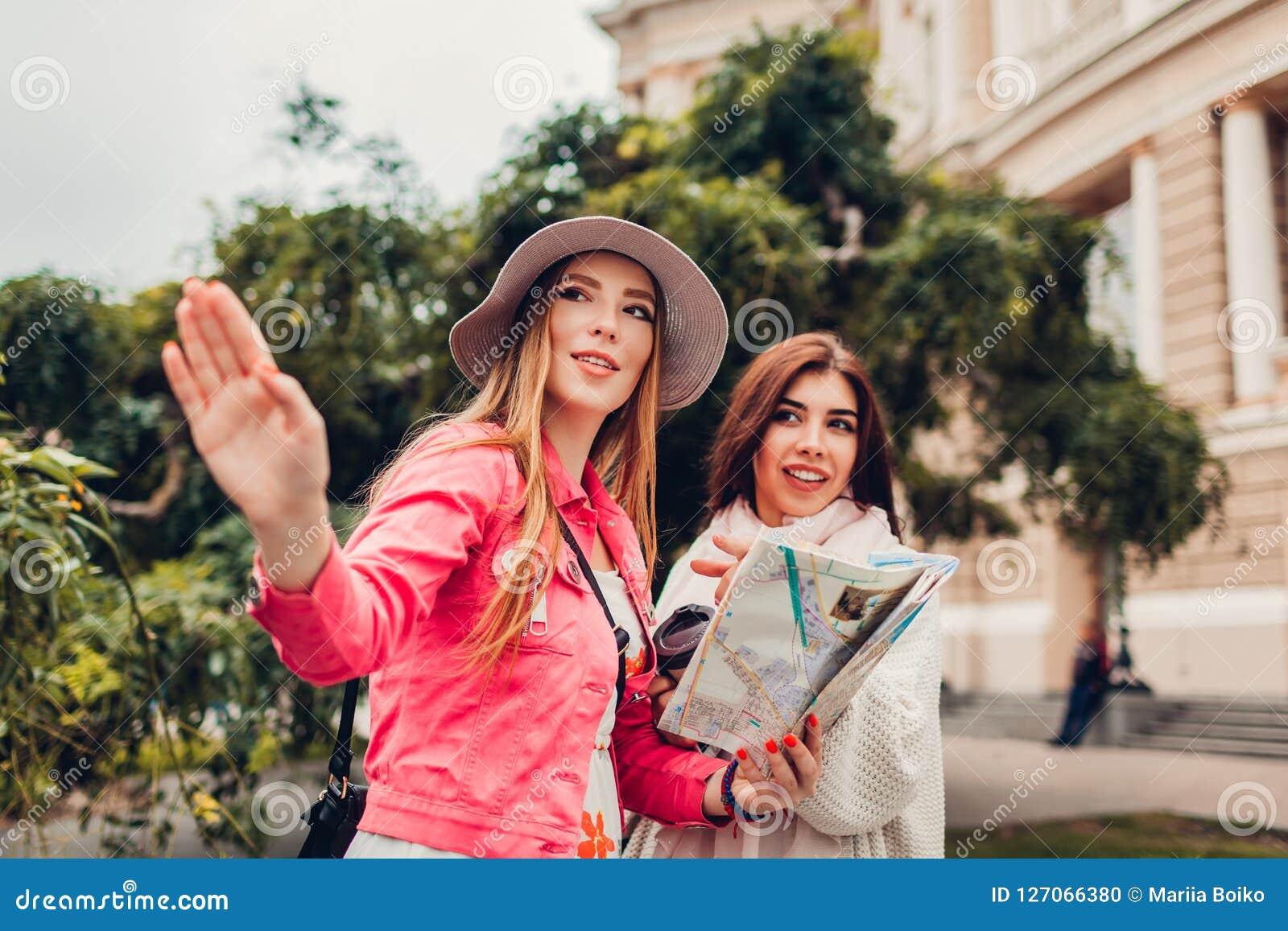 Twee vrouwentoeristen die naar juiste manier zoeken die kaart in Odessa gebruiken door operahuis Het gelukkige vriendenreizigers