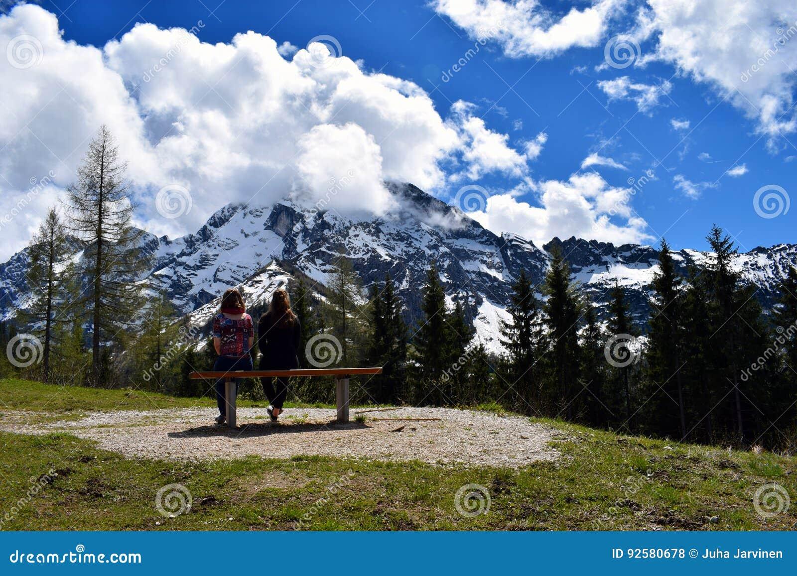 Twee vrouwenzitting op bank en het letten op mooie bergmening van Duitse Alpen
