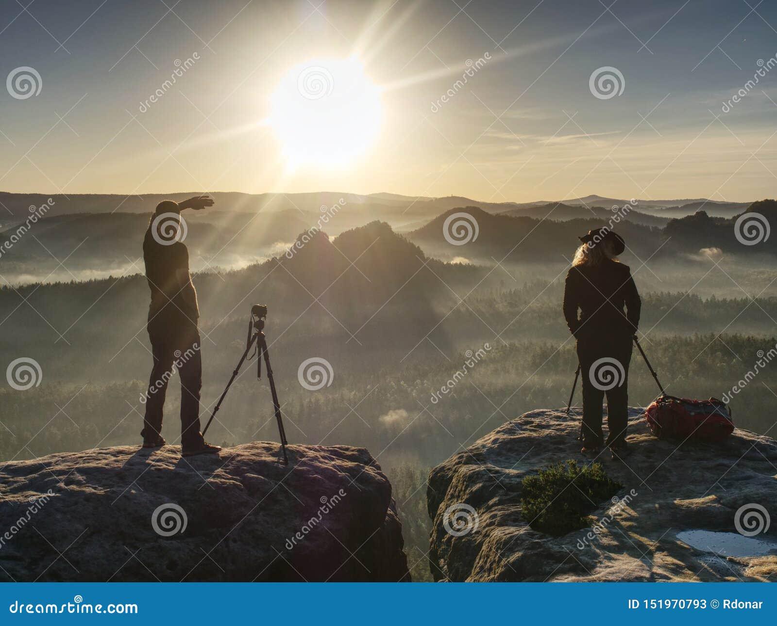 Twee wandelaars die beelden en bespreking bovenop berg nemen Twee fotografen