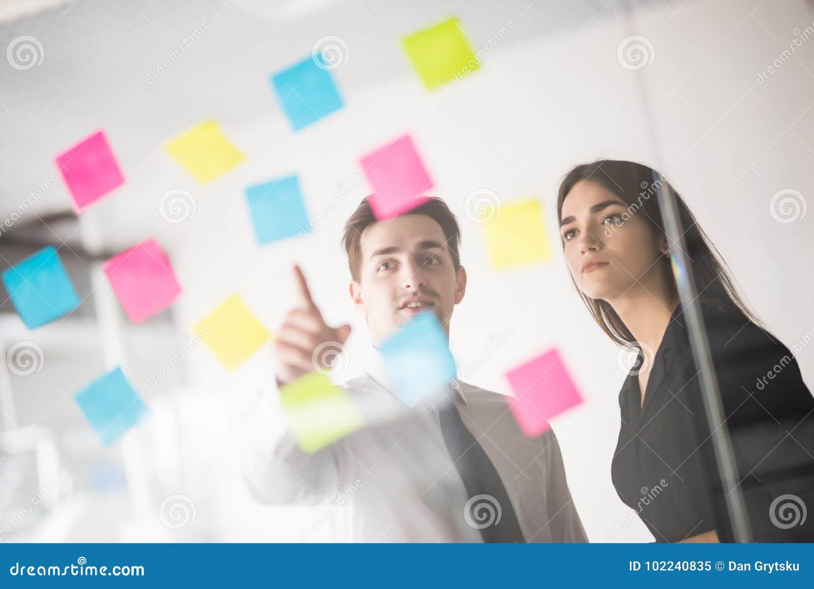 Twee zakenlui die en concept bespreken plannen Voorzijde van de teller en de stickers van de glasmuur Startbureau