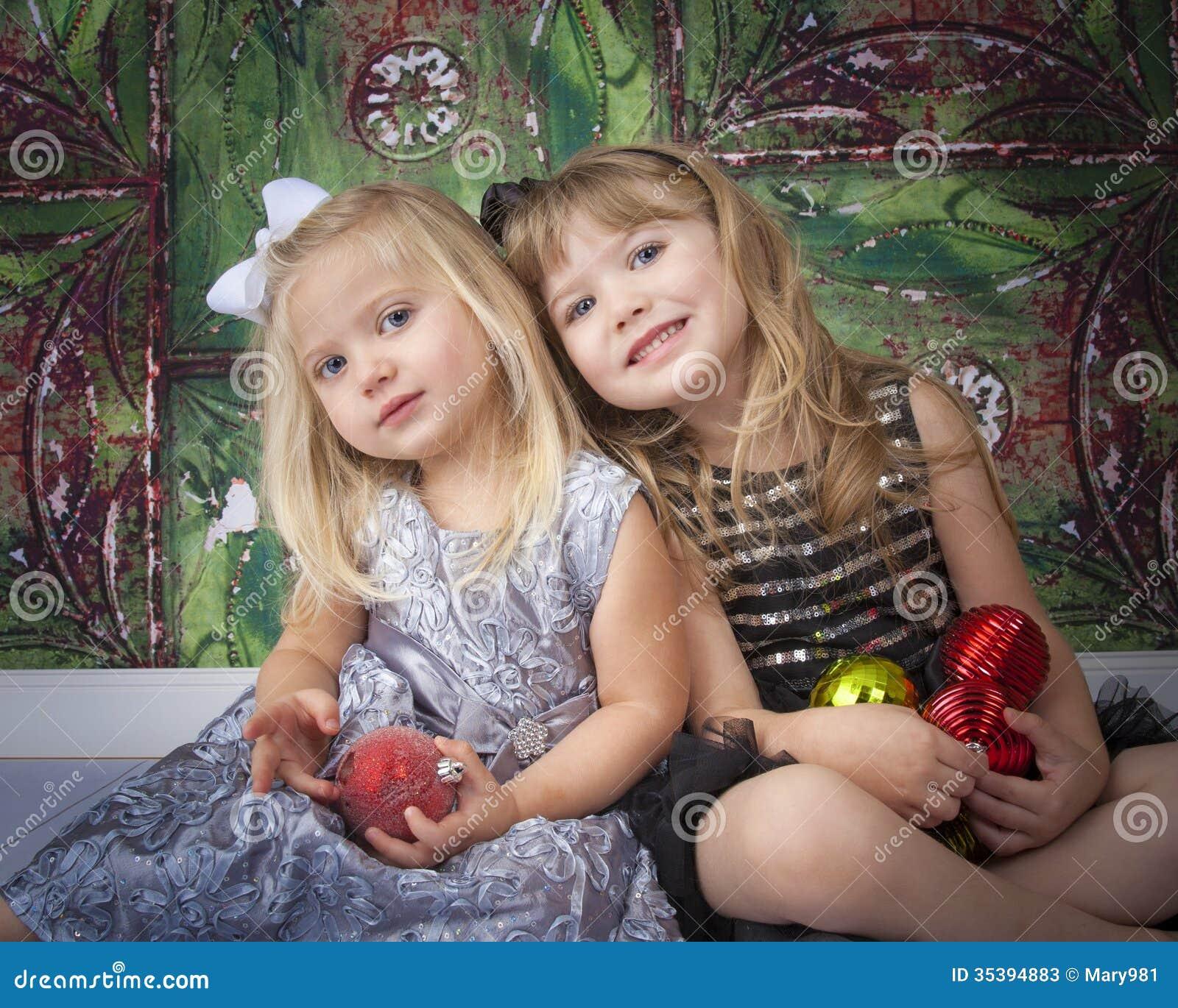 Twee Zusters die voor Kerstmisbeelden stellen