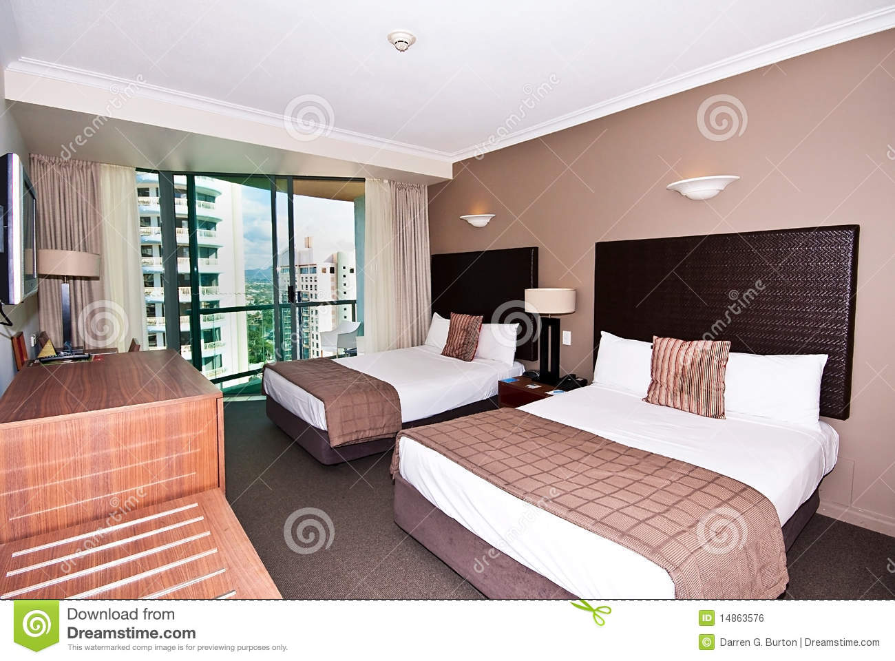 Twin double beds in a modern hotel room.