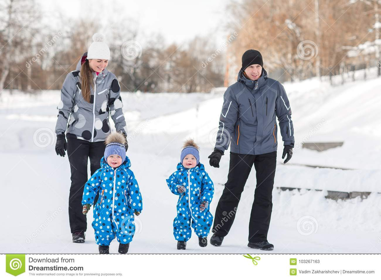Twin boys walking in the winter, parents are going back