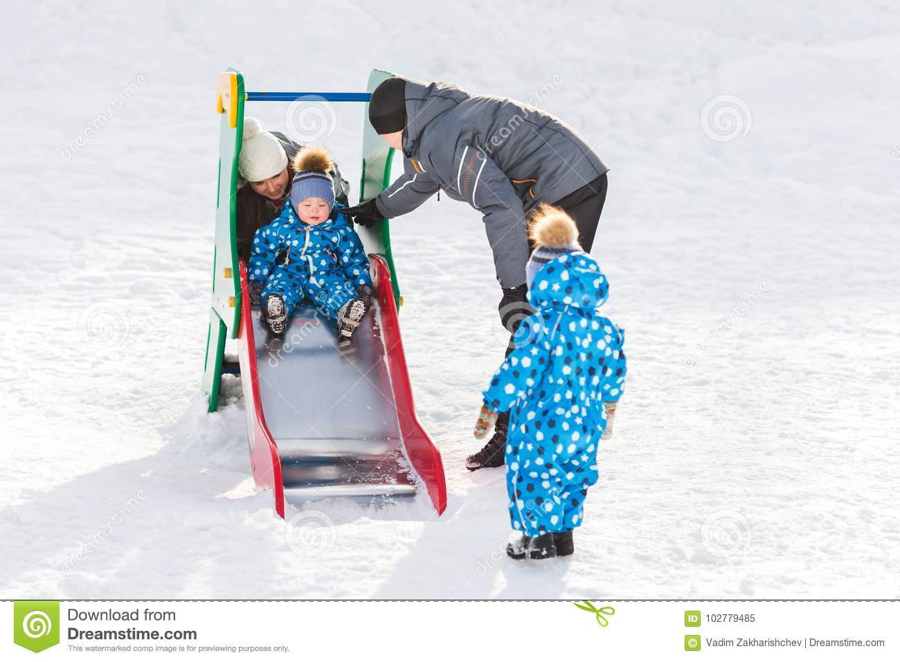 Twin brother rolls down hill, happy family winter walks in the Park