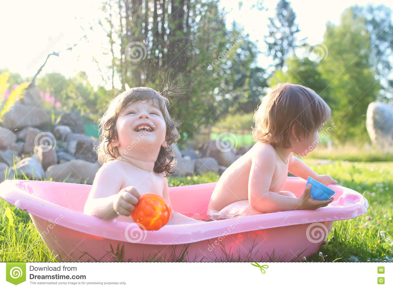 Twins boy and girl in bath water outdoor