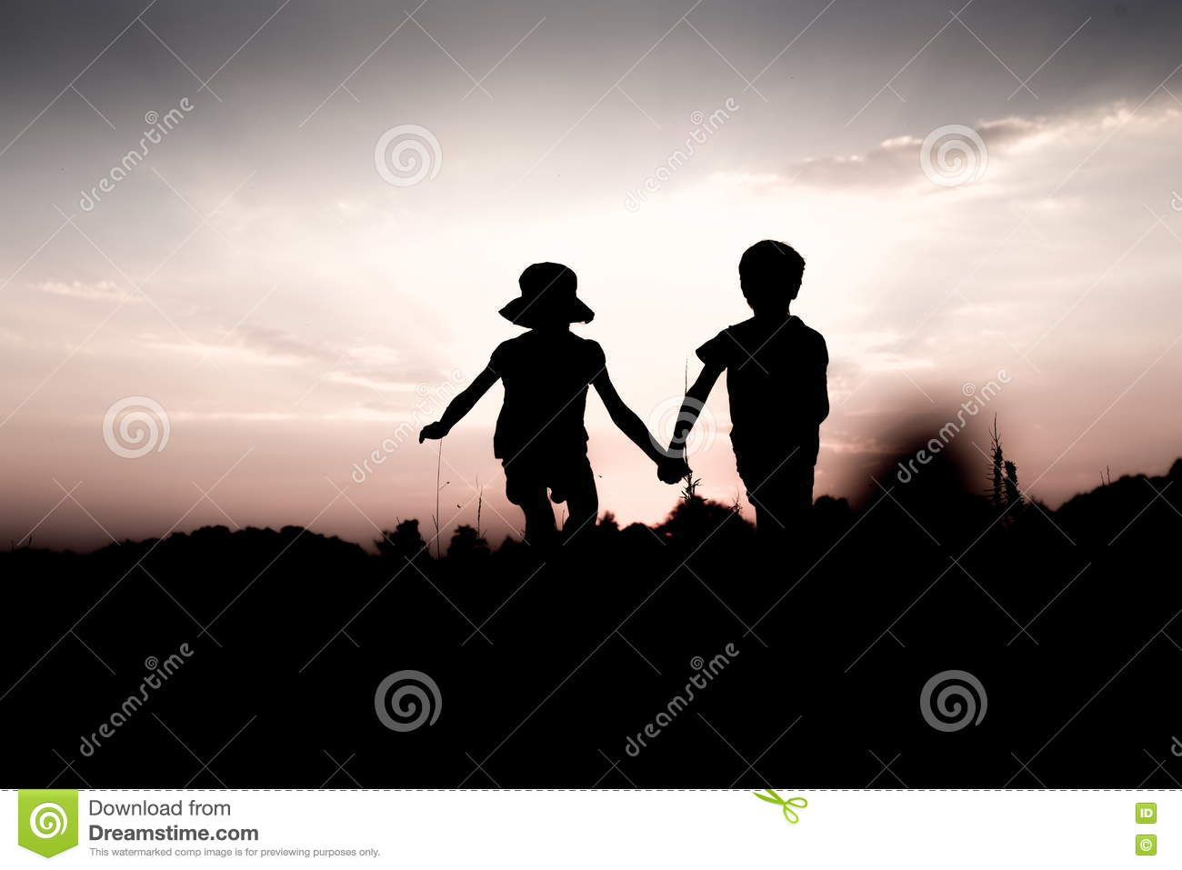 Twins jump off a hill holding hands at sunset