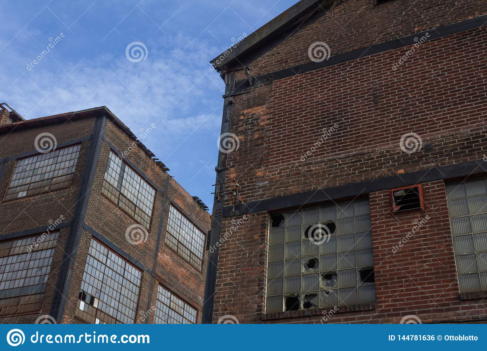 Two abandoned industrial buildings against a blue sky