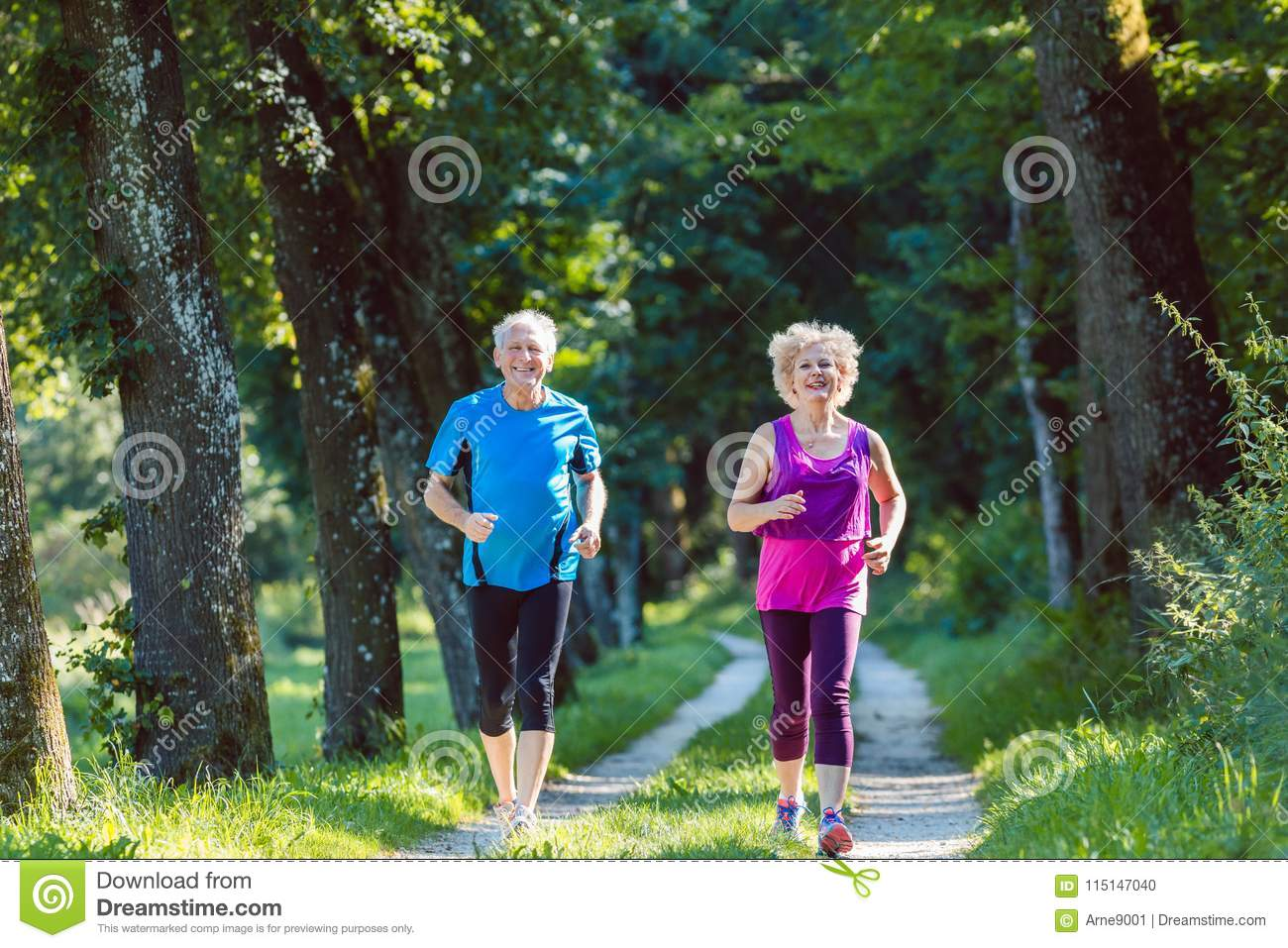 Two active seniors with a healthy lifestyle smiling while jogging