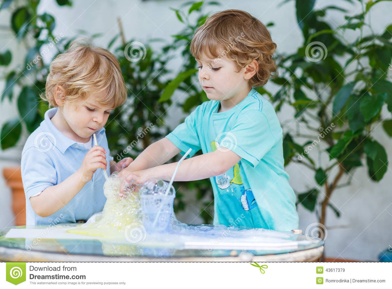 Two adorable boys making experiment with colorful bubbles