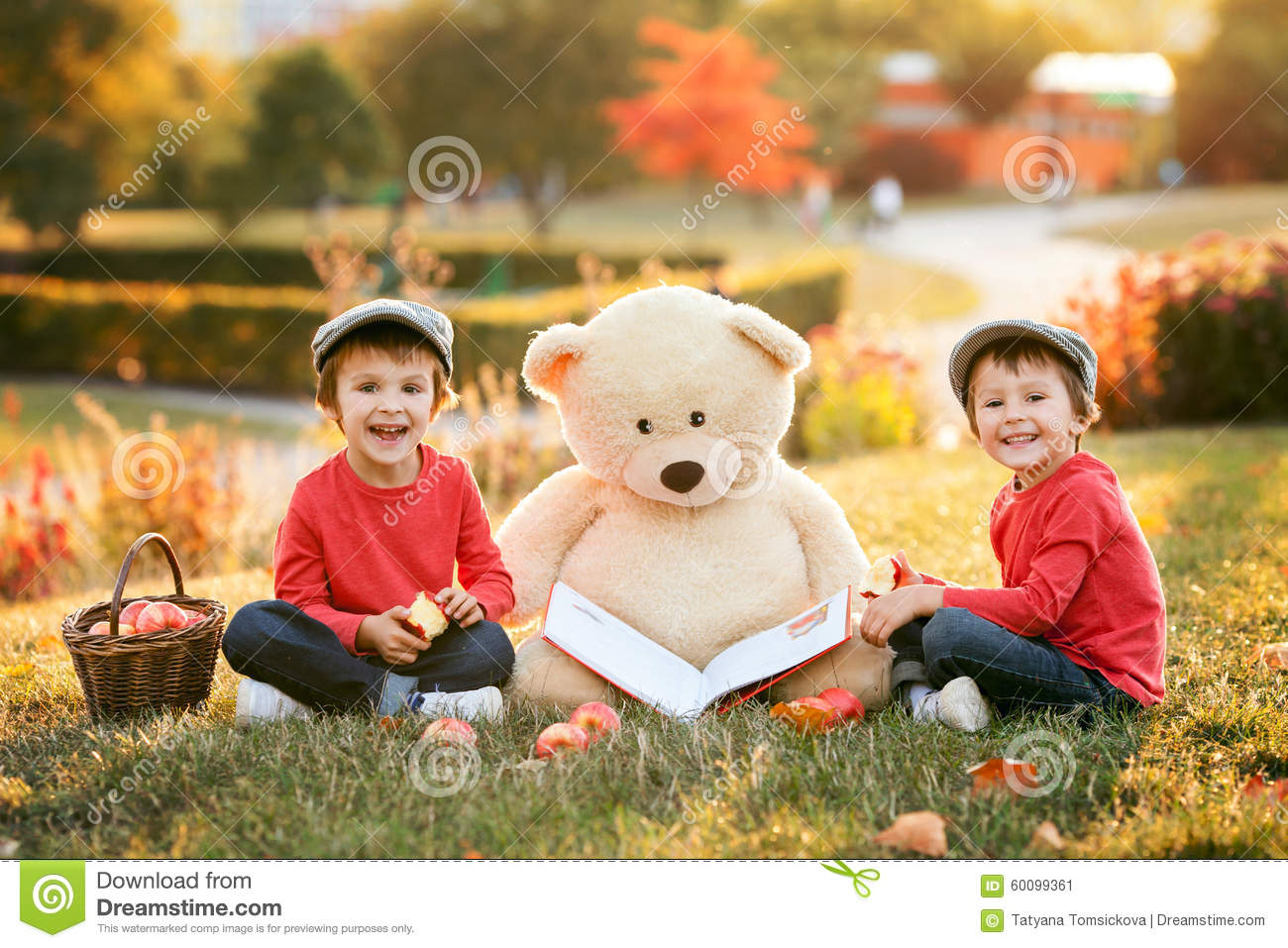 Two adorable little boys with his teddy bear friend in the park