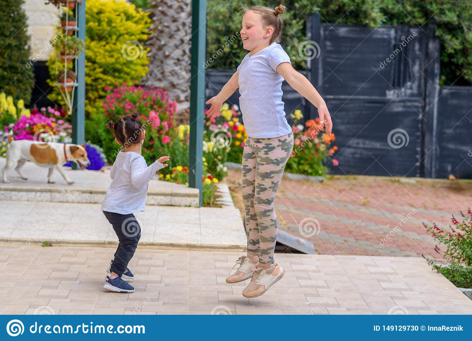 Full length portrait of attractive, playful, cheerful, happy comic couple children jumping over nature background.