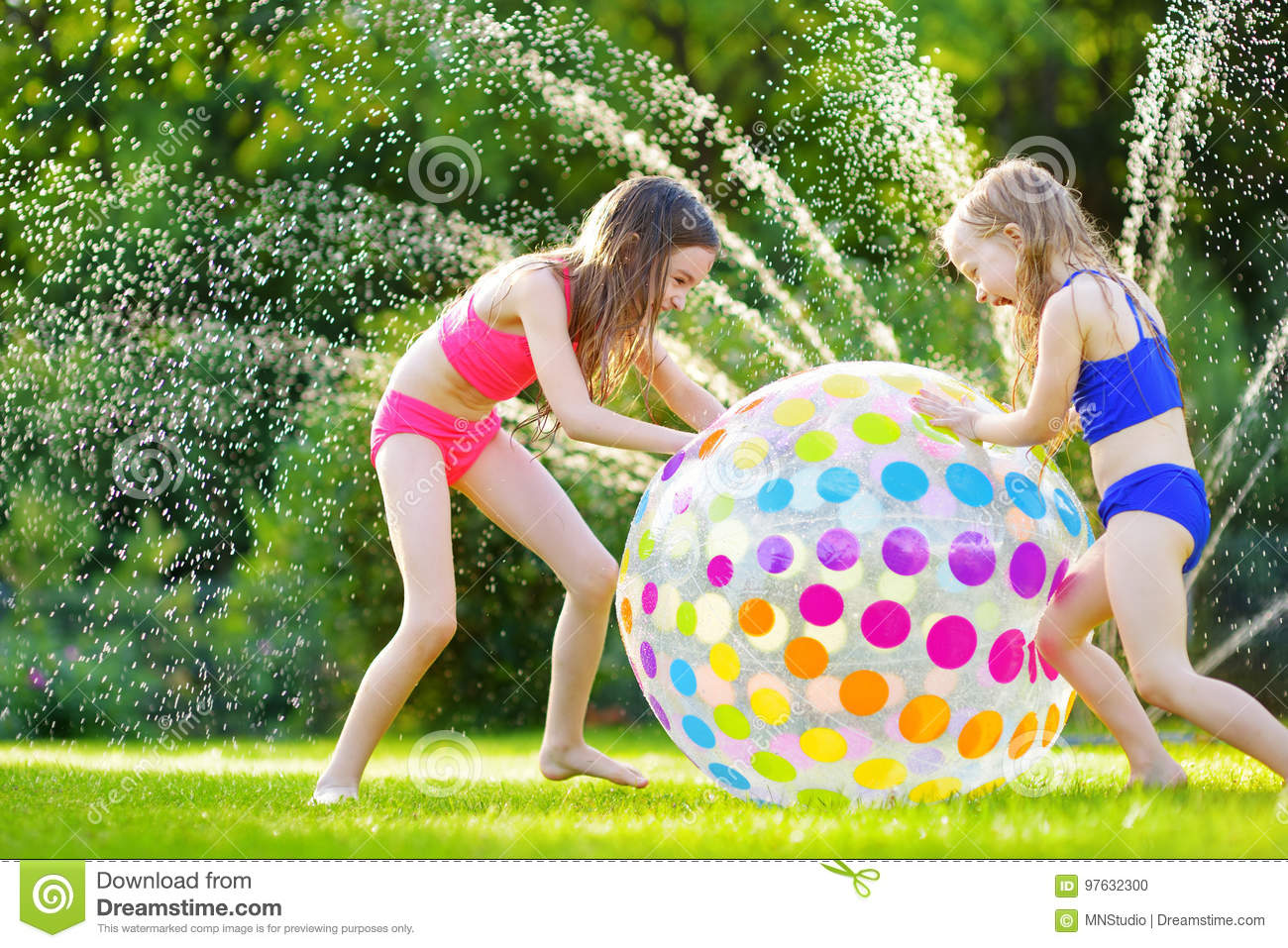 two adorable little girls playing with inflatable beach ball in a backyard on sunny summer day