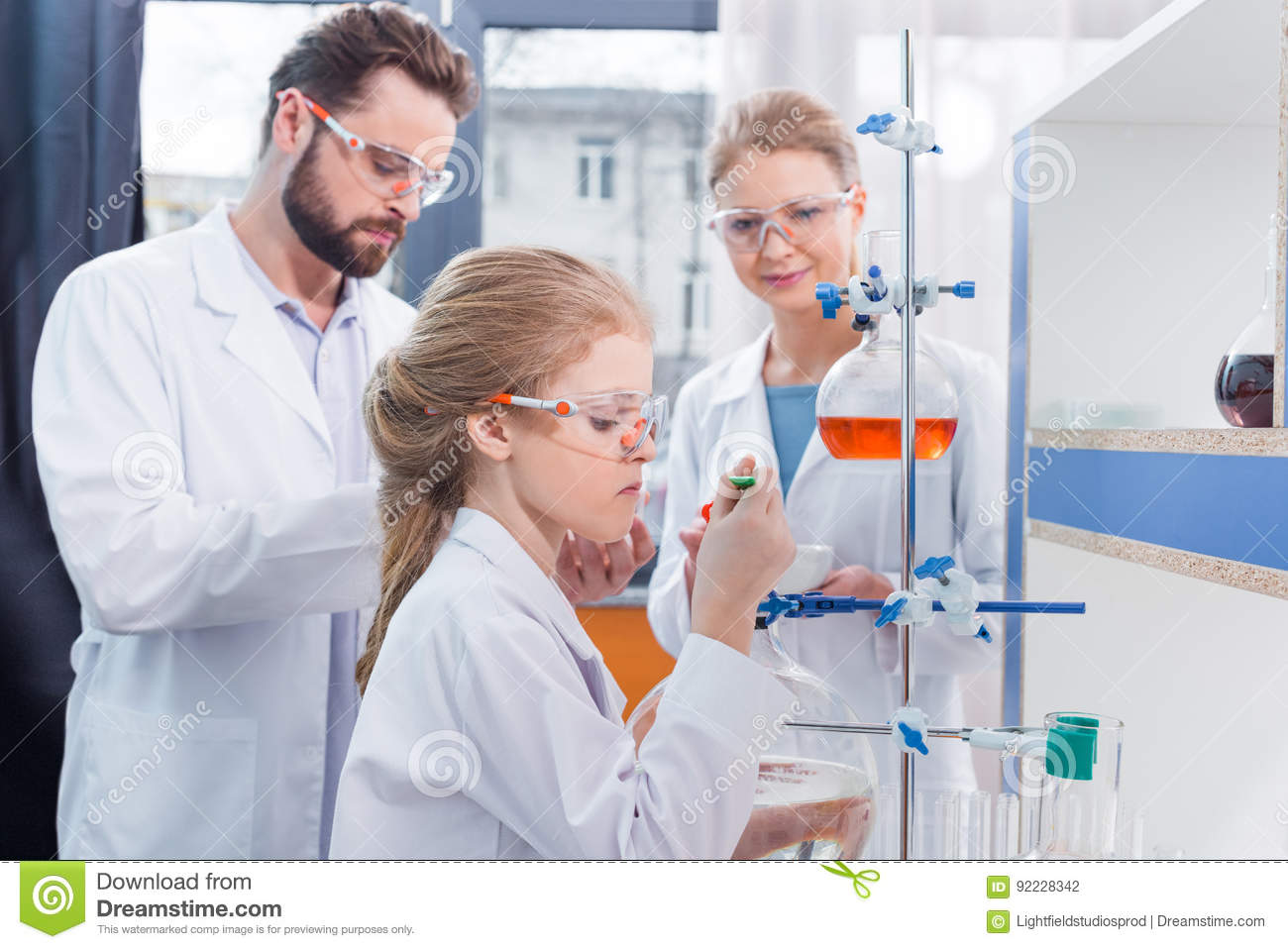 Two adult scientists and little girl student making experiment