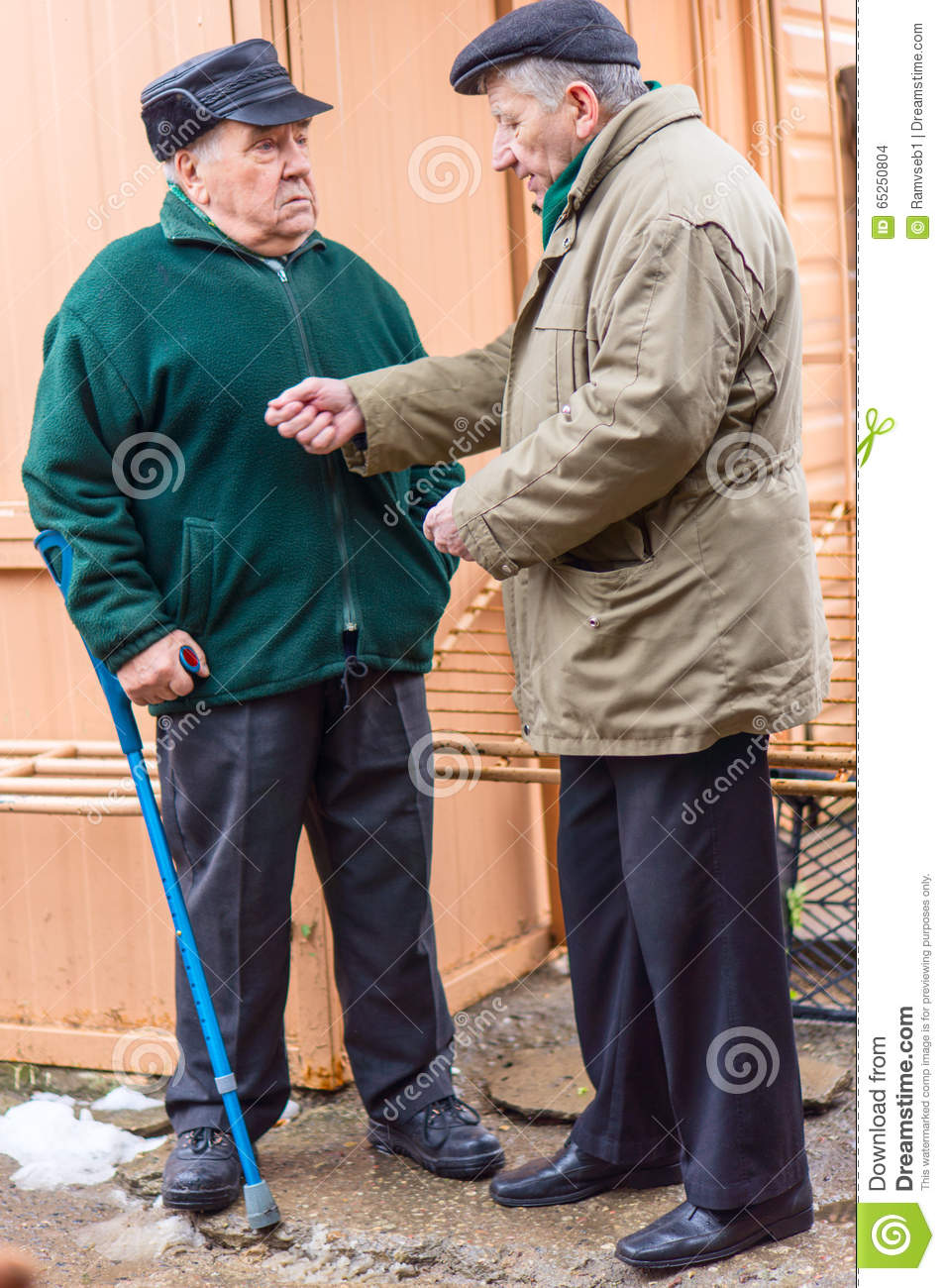 Two aged men discuss in the street