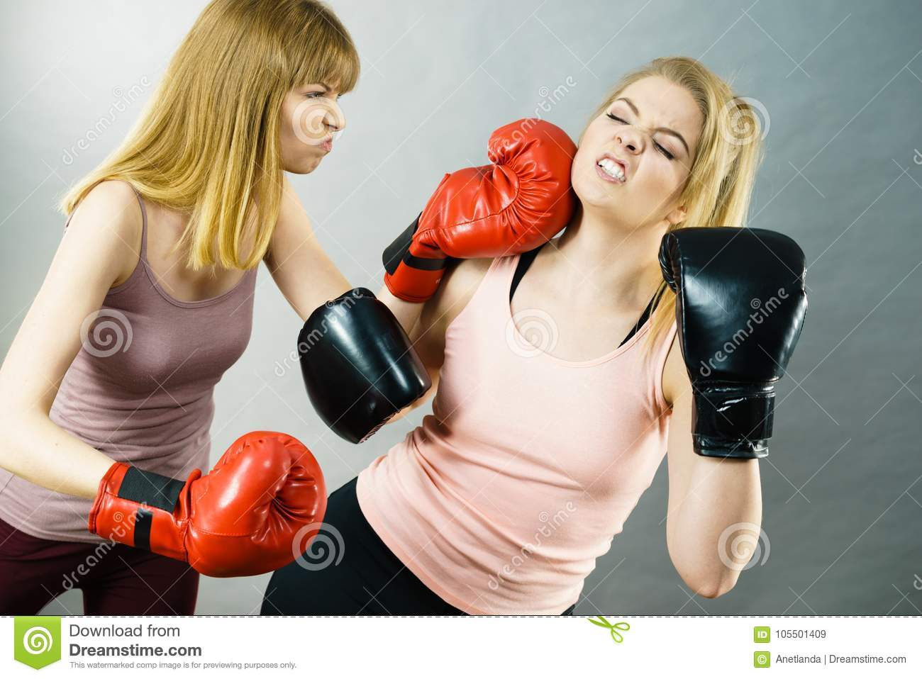 fbd9eafe4 Two agressive women wearing boxing gloves having argue fight being mad at each  other. Female violance concept.
