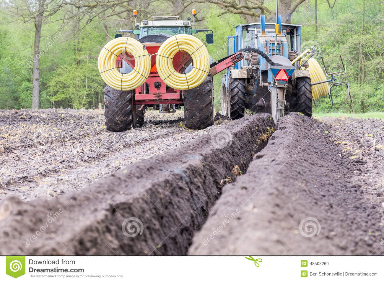 Two agriculture tractors digging drainage pipes in ground for Digging ground dream meaning
