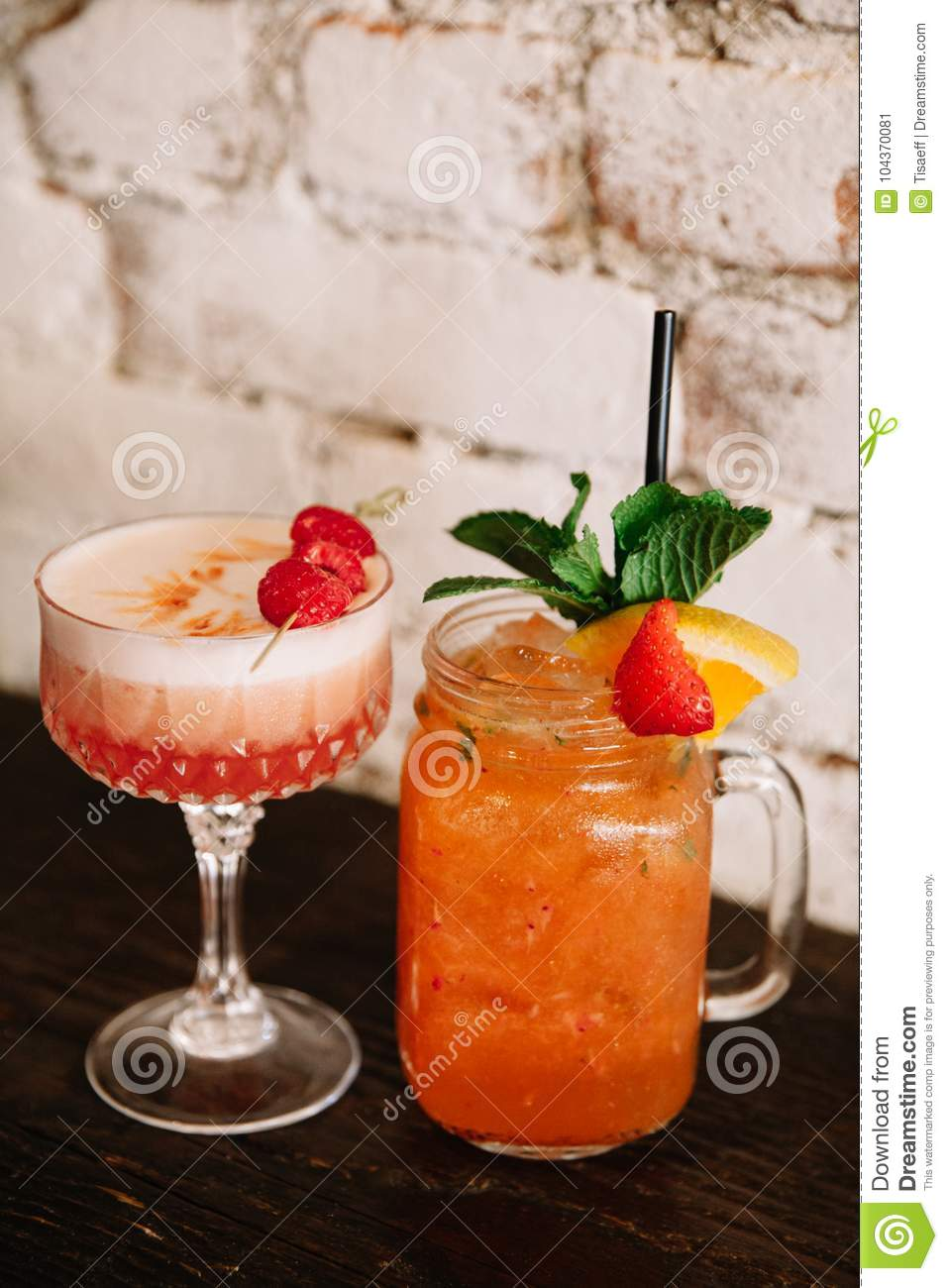 Two alcoholic cocktails garnished with berries against the white