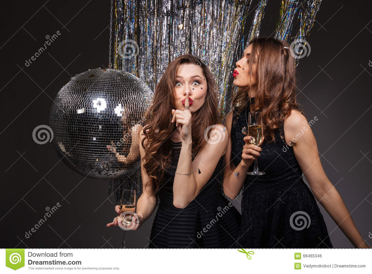 Two amusing women showing silence gesture and drinking champagne
