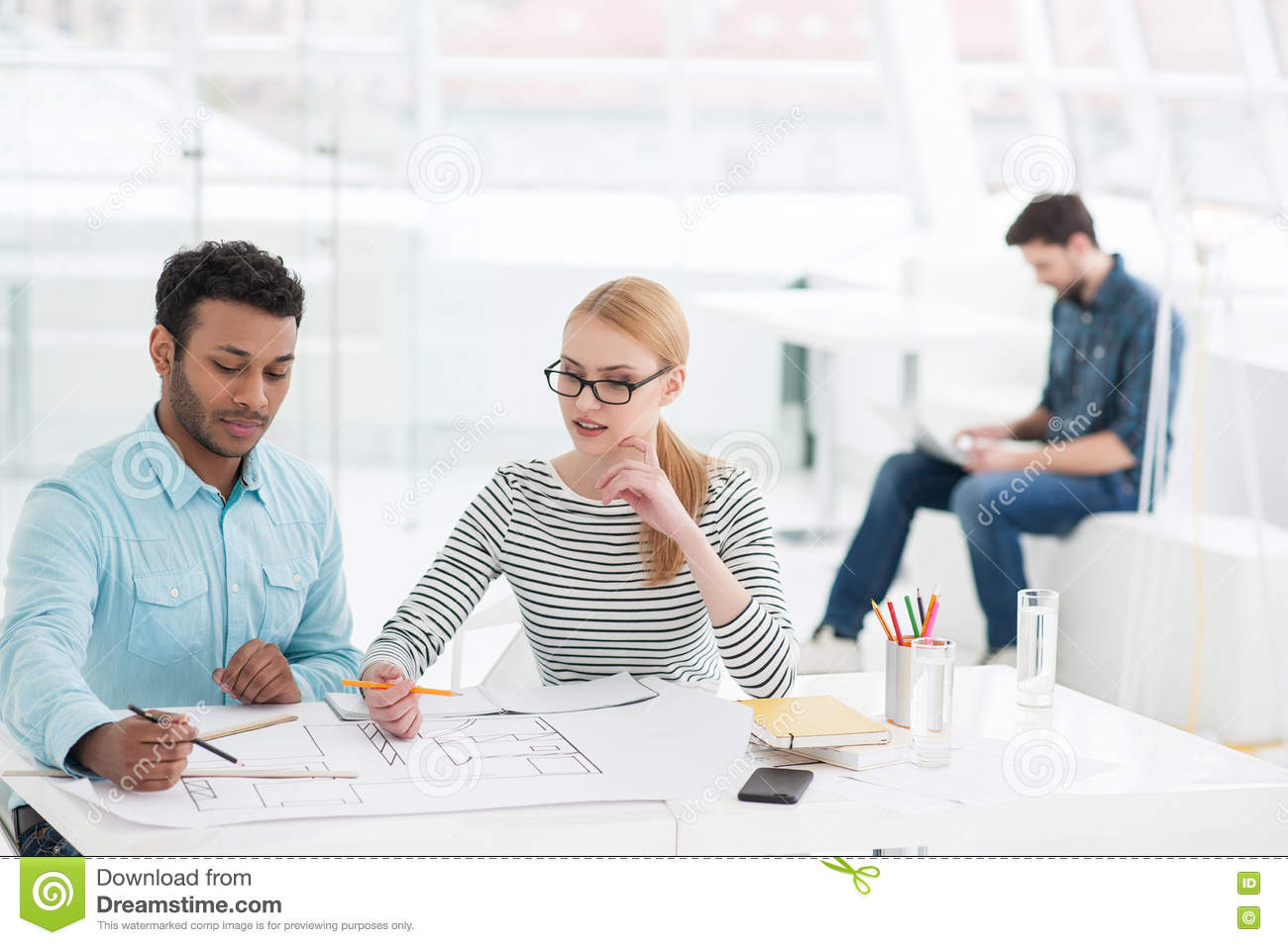 Two architects discussing details of blueprin