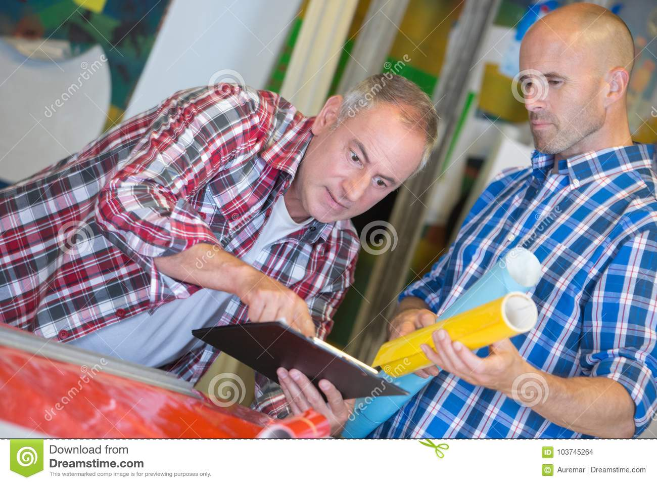 Two architects looking at clipboard working in office