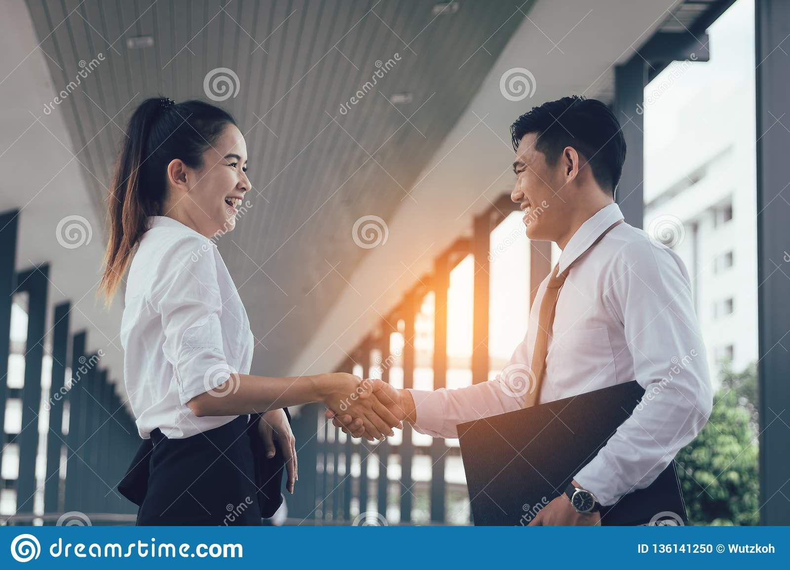 Two asian business people standing and shaking hands with together