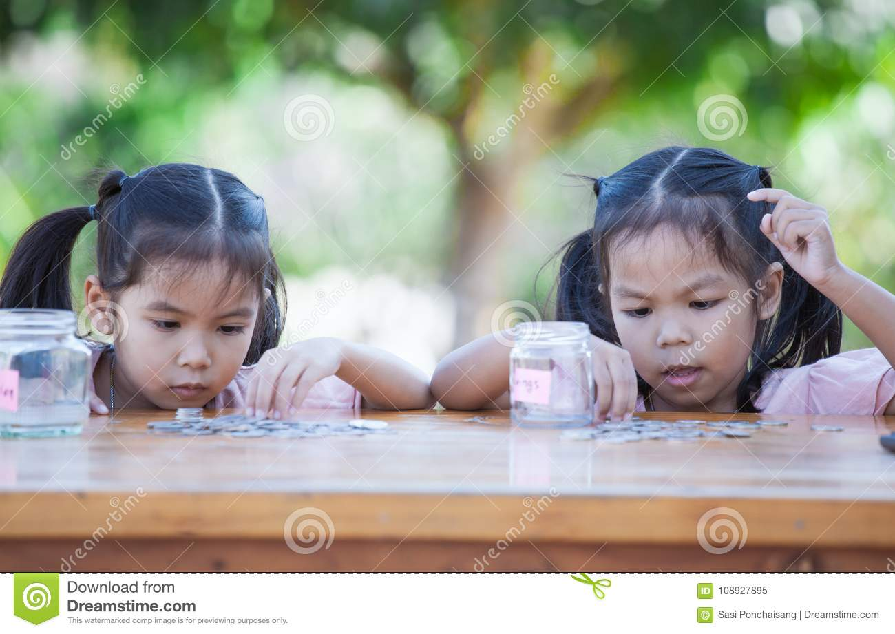 Two asian child girls counting and putting coin into bottle