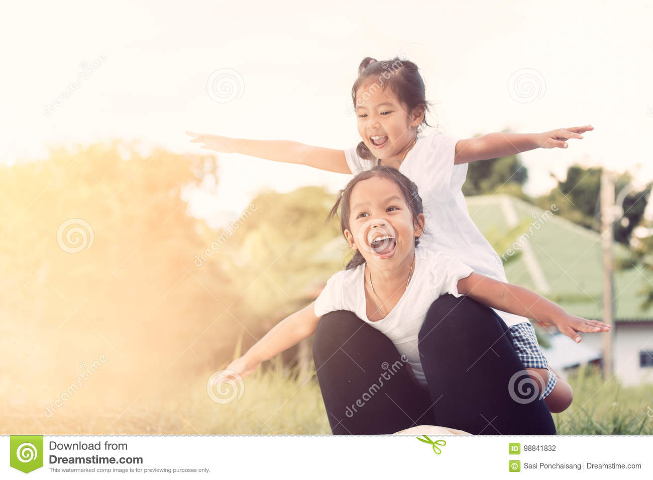 Two asian child girls having fun to fly on mother`s leg