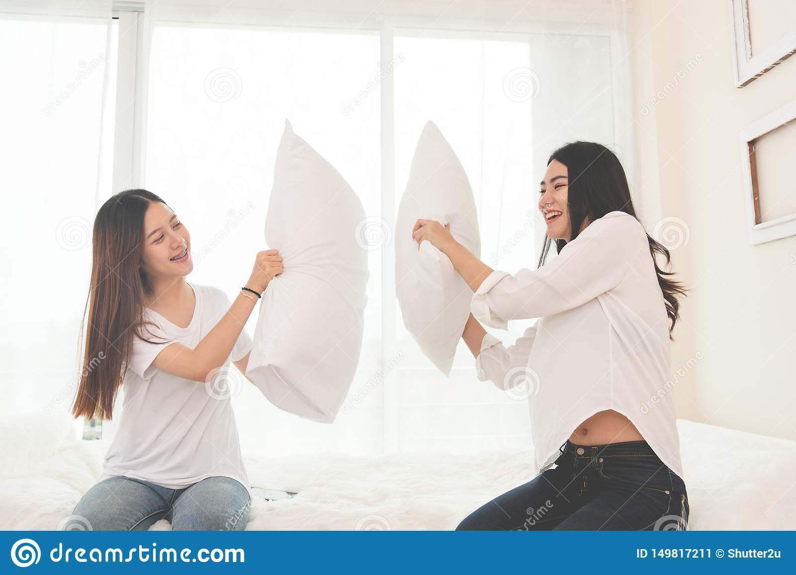 Two Asian doing pillow fight in bedroom. Lifestyles and People concept. Relation and friendship theme