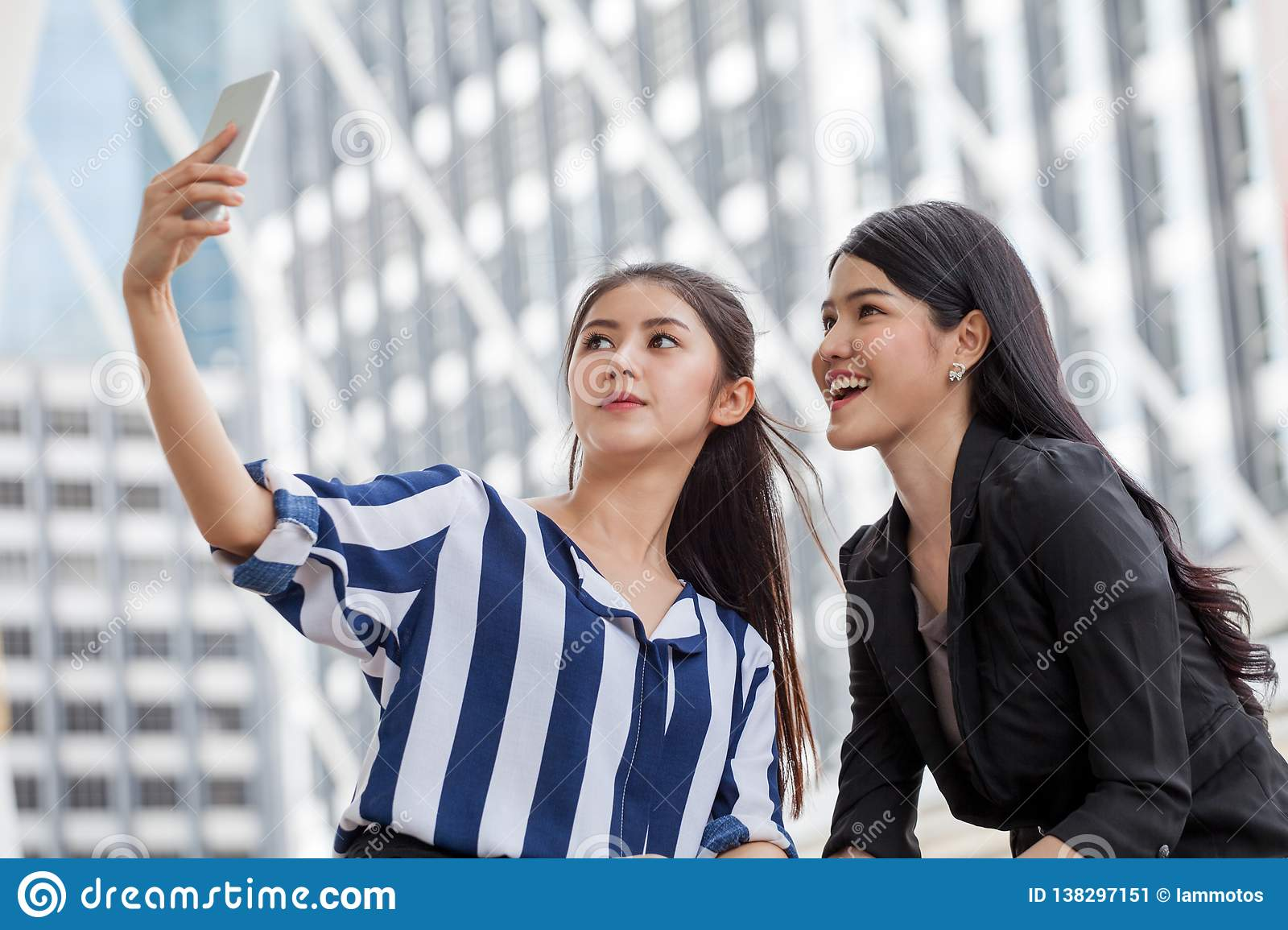 Two asian girls friends taking selfie photo with smartphone in urban