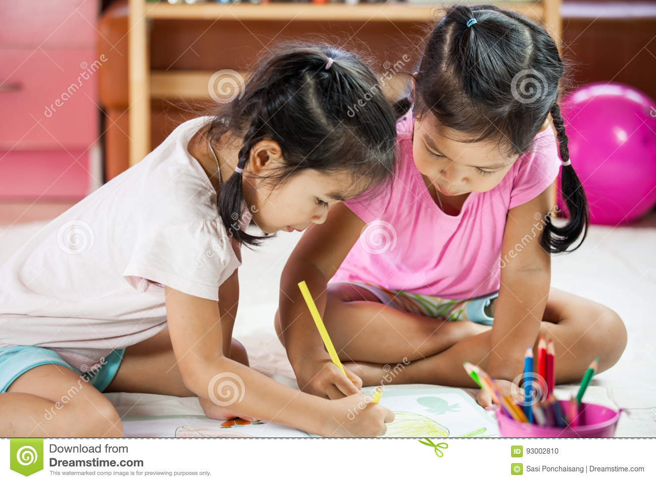 Two asian little girls having fun to paint with crayon