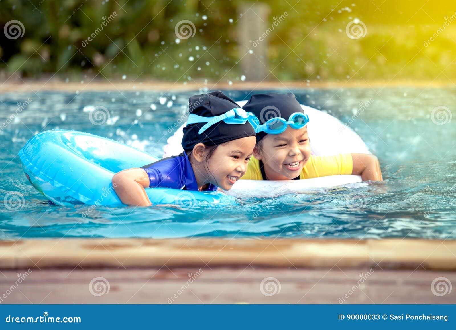 Two asian little girls having fun to swim in swimming pool
