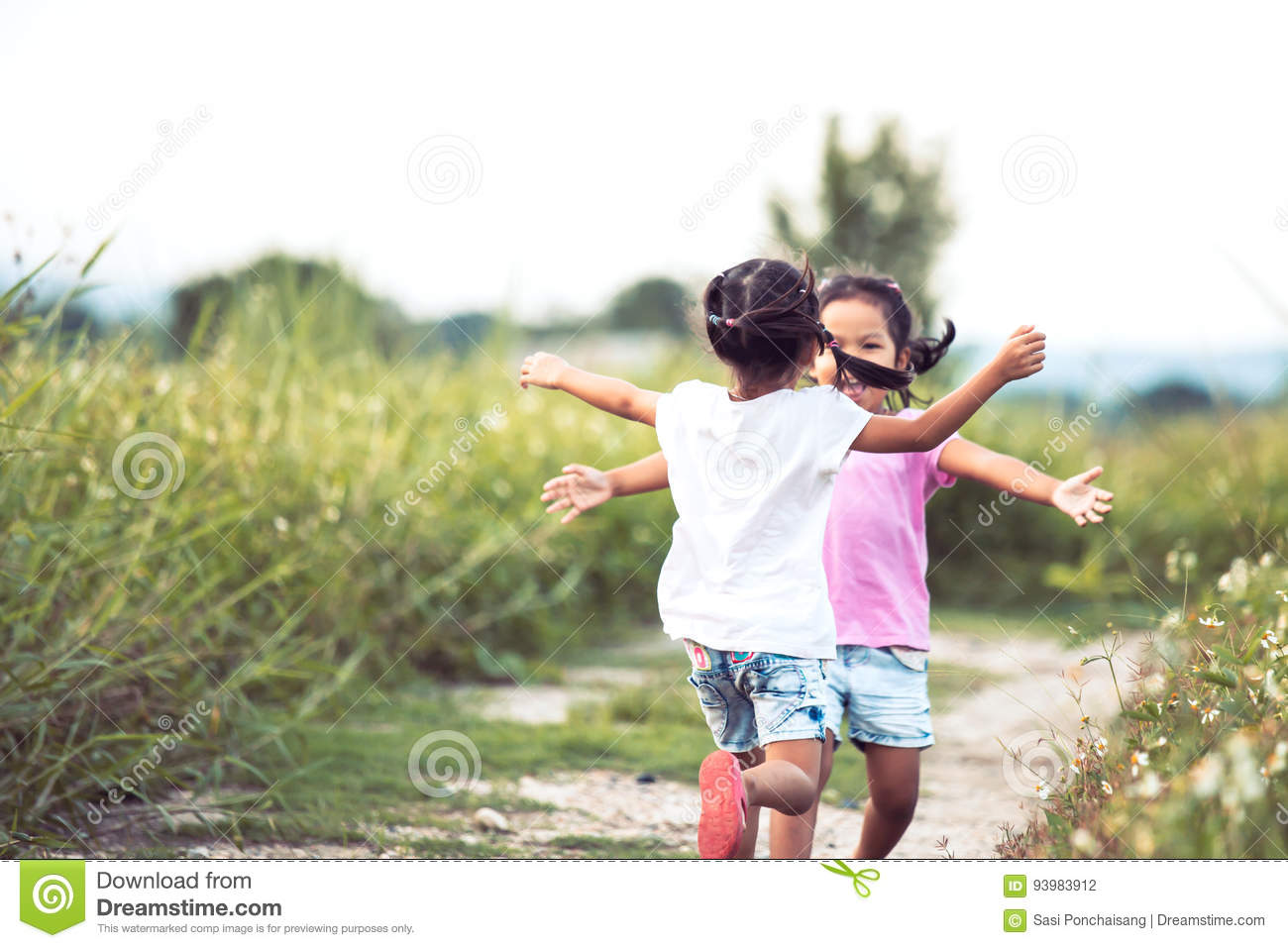 Two asian little girls running to give a hug each other