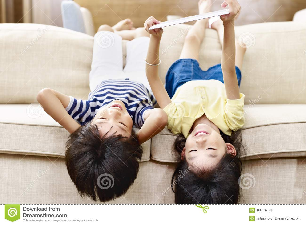 Pleasing Two Asian Little Kids Lying Upside Down On Couch Stock Photo Machost Co Dining Chair Design Ideas Machostcouk