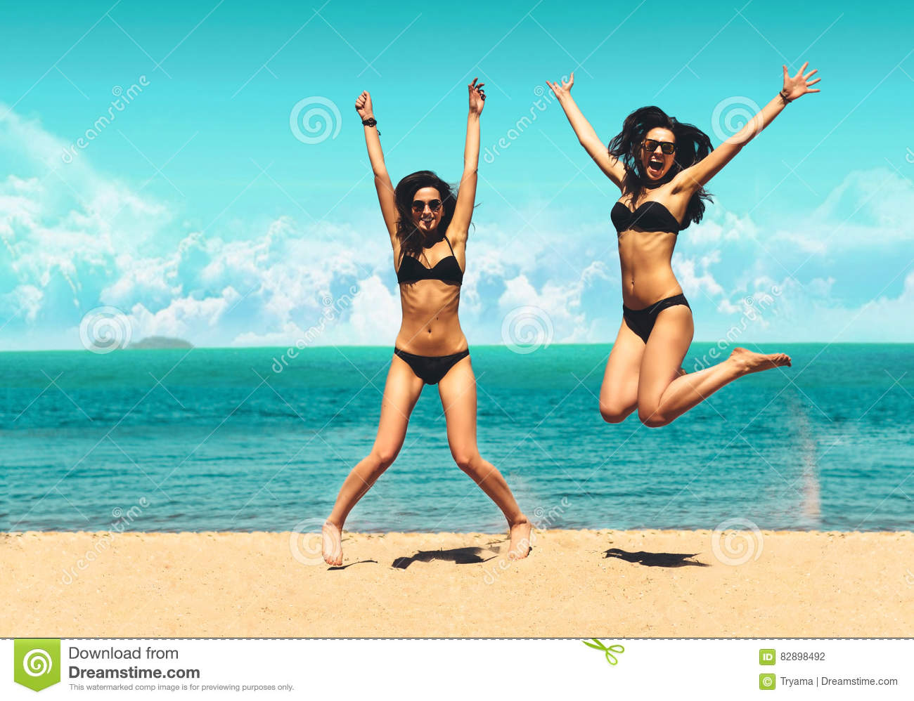 Two Attractive Girls In Bikinis Jumping On The Beach Best Friends Having Fun Summer Vacation Holiday Lifestyle Happy