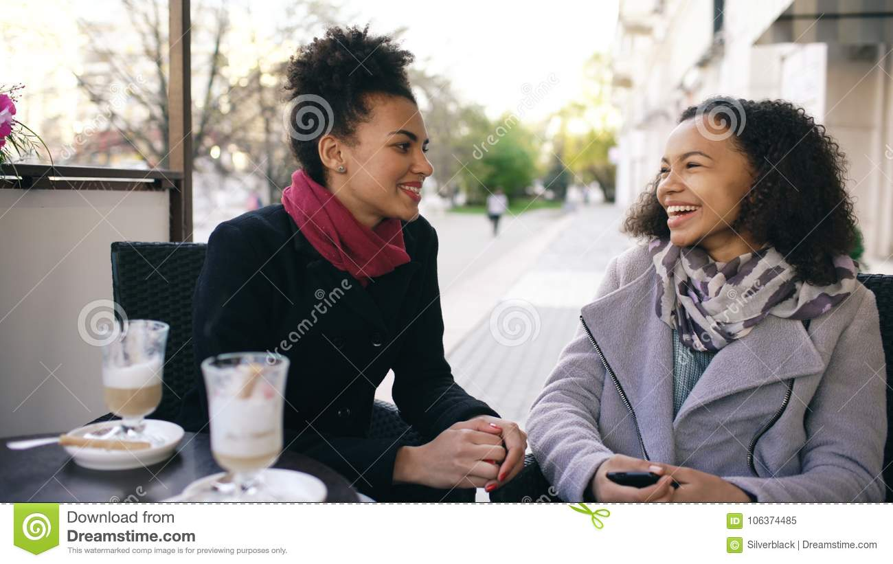 Download Two Attractive Mixed Race Women Talking And Drinking Coffee In Street Cafe. Friends Have Fun After Visiting Mall Sale Stock Image - Image of drink, cafe: 106374485
