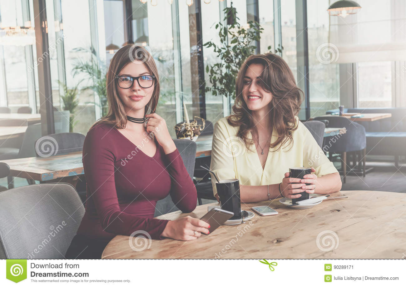 Download Two Attractive Young Brunette Women Sit In Cafe At Table And Drink Coffee. Meeting Friends At Restaurant. Stock Image - Image of girls, lifestyle: 90289171