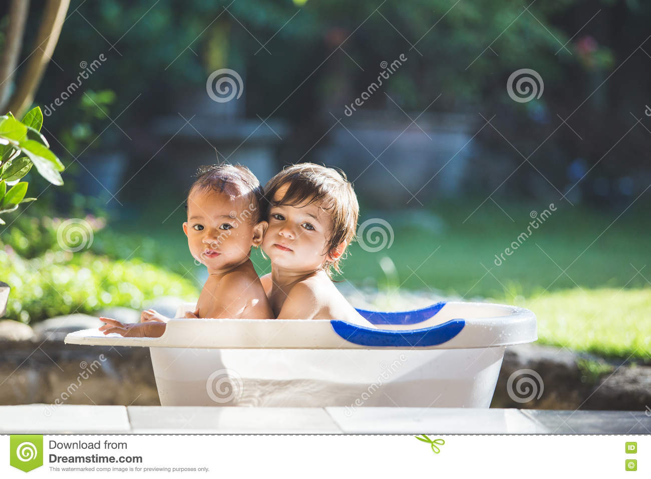 Two babies taking a bath together
