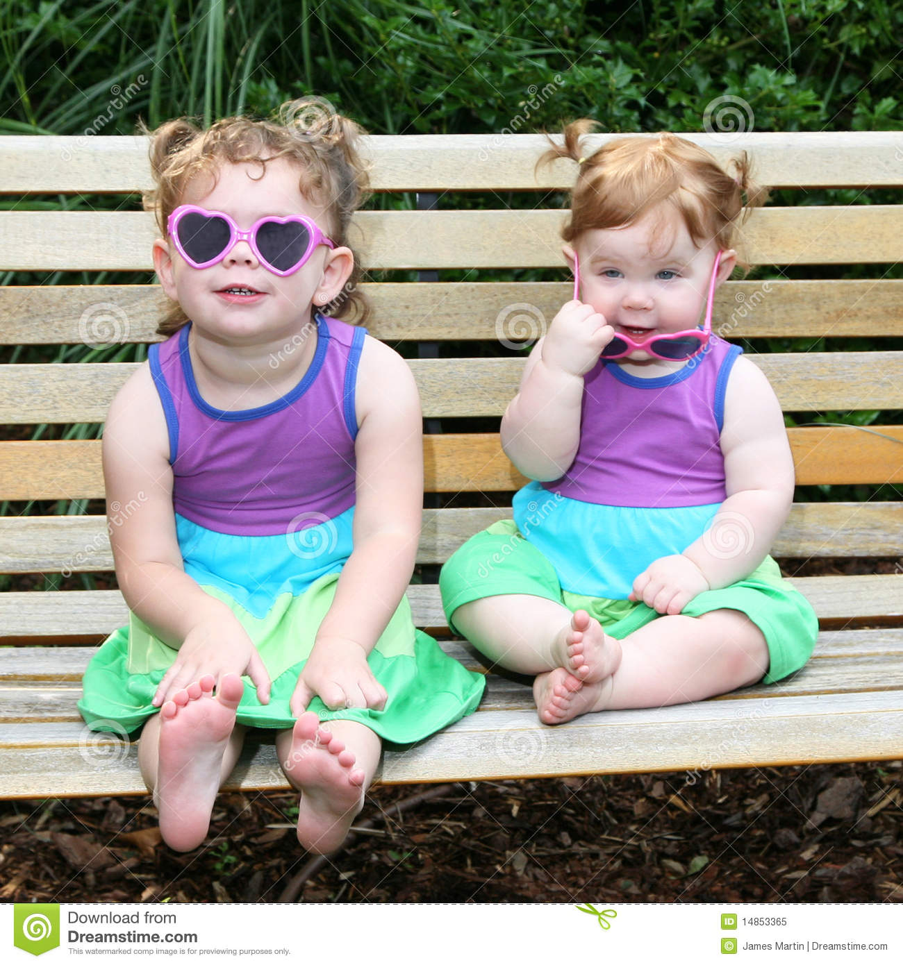 Two baby girls in sunglasses and sun dresses