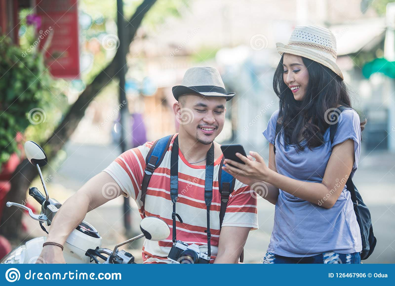 Two backpackers with summer hat seeing the result of their photo