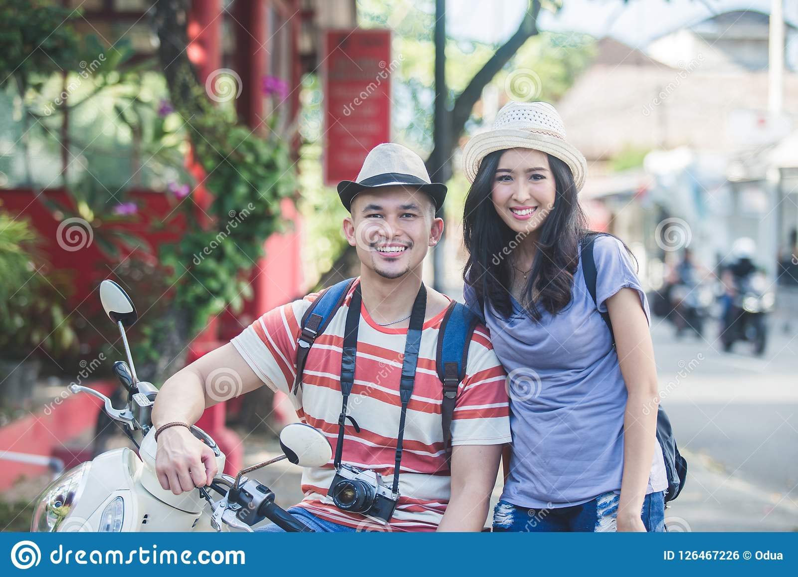 Two backpackers with summer hat smiling to camera while sitting