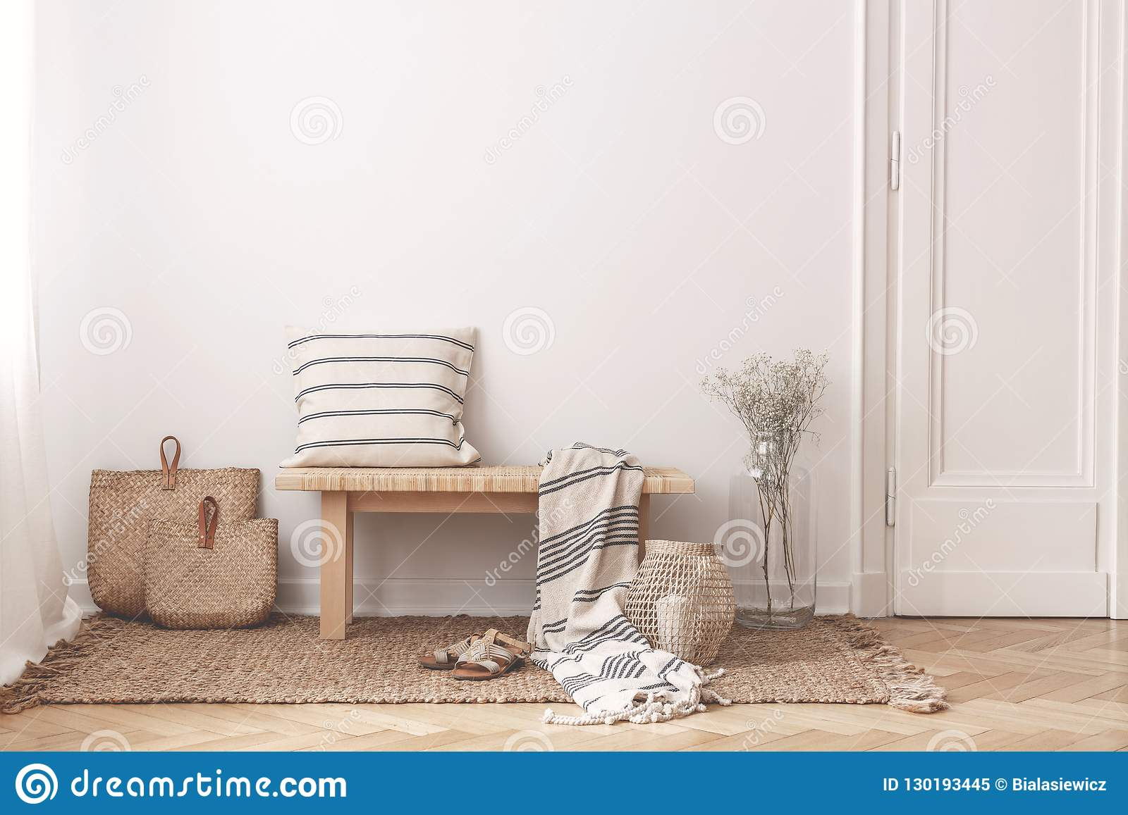 Two bags made of straw next to wooden table with striped pillow
