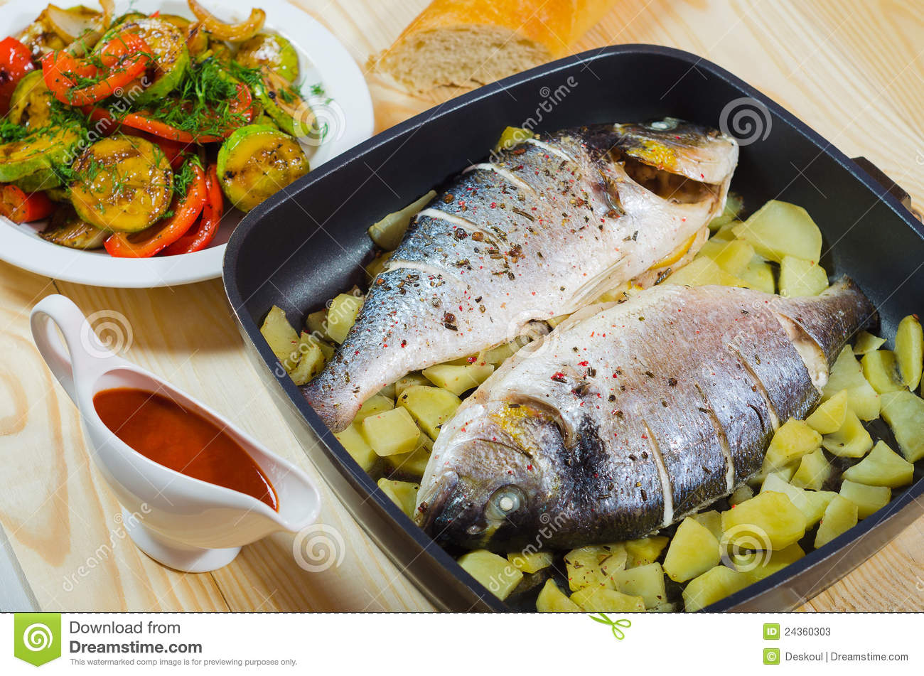 Two baked fish in pan sauce and vegetables stock photos for Pan grilled fish